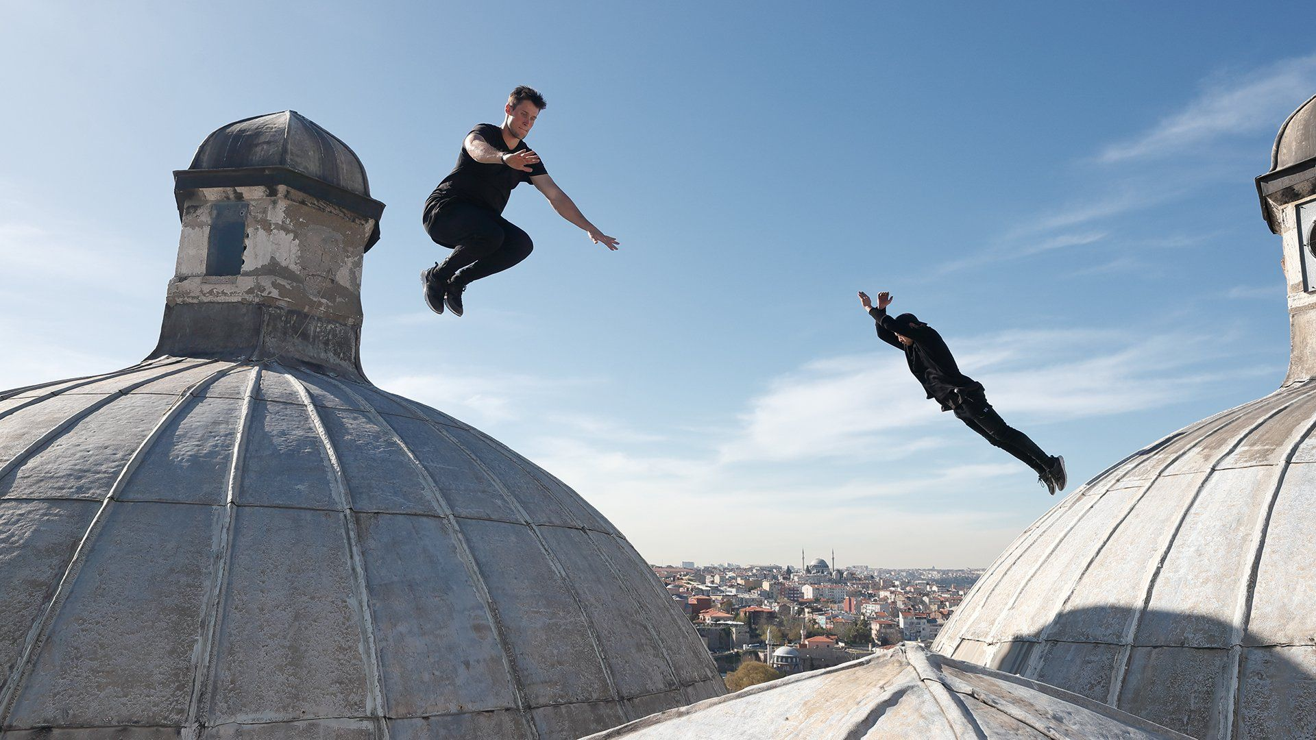 2 young men dressed in black leap around on a rooftop between Turkish domes with stone lanterns on top